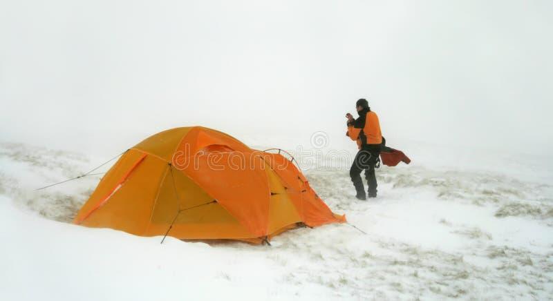 Uomo vicino alla tenda nella bufera di neve della neve fotografia stock libera da diritti