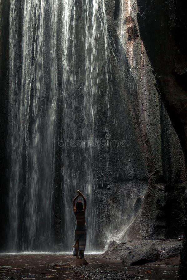 Uoung kvinnafotvandrare som ser vattenfallet i djungler Flicka för lopp för Ecotourismbegreppsbild man för bali town för solnedgå royaltyfria foton