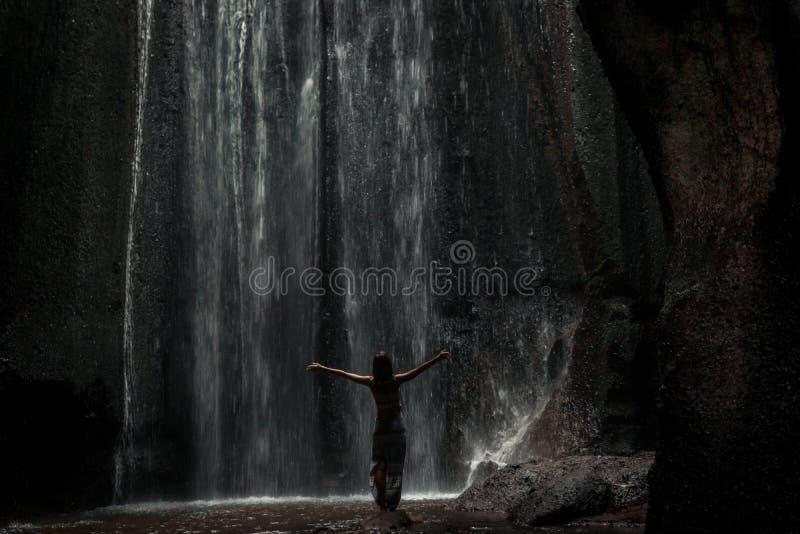 Uoung kvinnafotvandrare som ser vattenfallet i djungler Flicka för lopp för Ecotourismbegreppsbild man för bali town för solnedgå royaltyfri fotografi