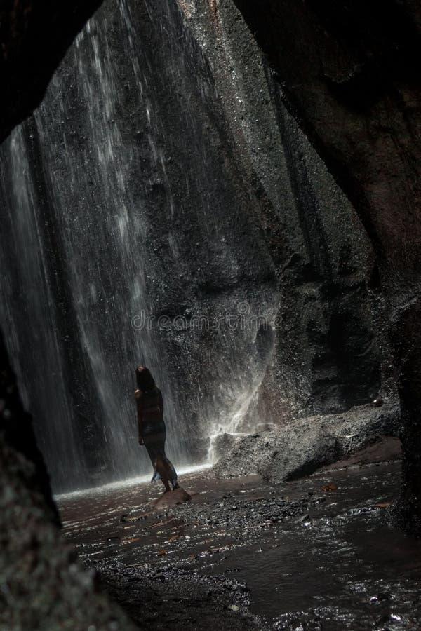 Uoung kvinnafotvandrare som ser vattenfallet i djungler Flicka för lopp för Ecotourismbegreppsbild man för bali town för solnedgå royaltyfri foto