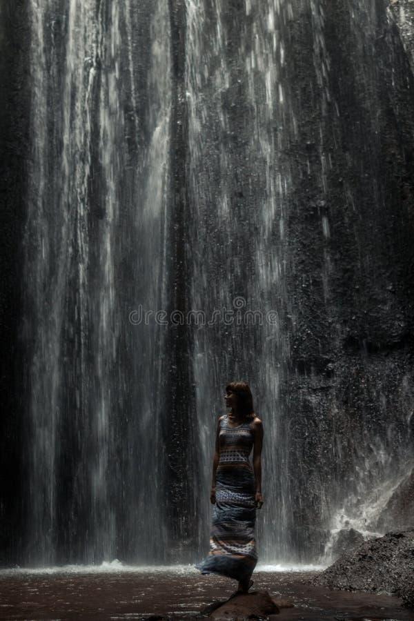 Uoung kvinnafotvandrare som ser vattenfallet i djungler Flicka för lopp för Ecotourismbegreppsbild man för bali town för solnedgå arkivfoton