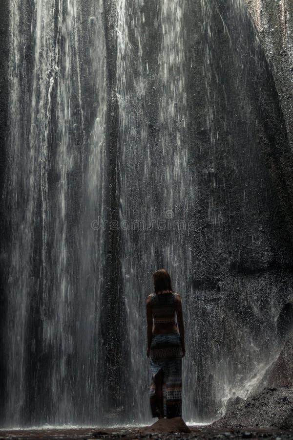Uoung kvinnafotvandrare som ser vattenfallet i djungler Flicka för lopp för Ecotourismbegreppsbild man för bali town för solnedgå arkivbild