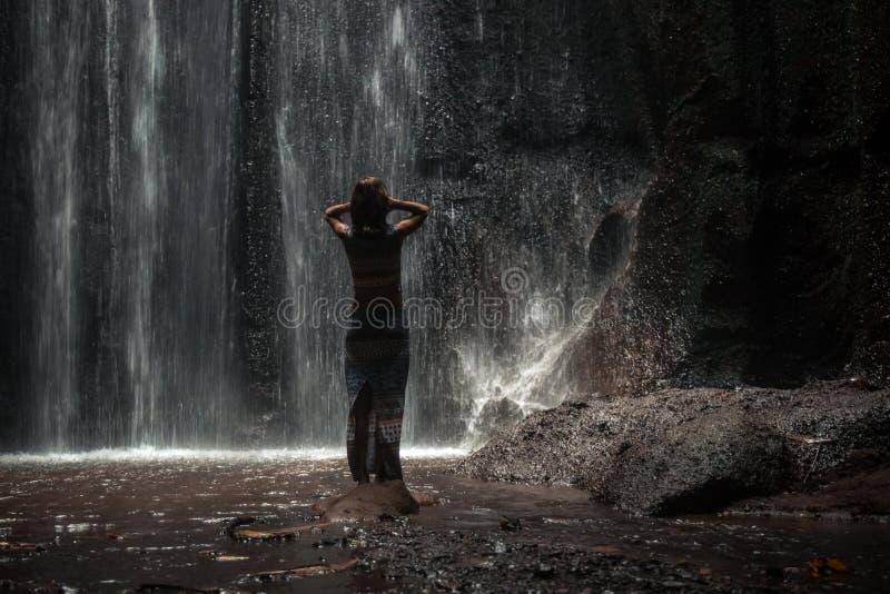 Uoungvrouw die backpacker de waterval in wildernissen bekijken Het meisje van de het beeldreis van het eco-toerismeconcept Het Ei stock fotografie