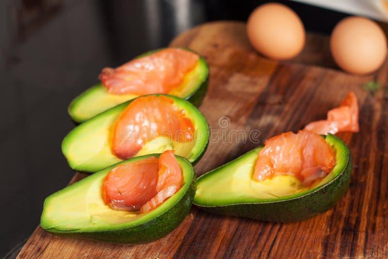 Uova al forno in avocado con il salmone affumicato fotografia stock libera da diritti