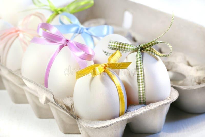 Uova bianche con i nastri colorati fotografie stock libere da diritti