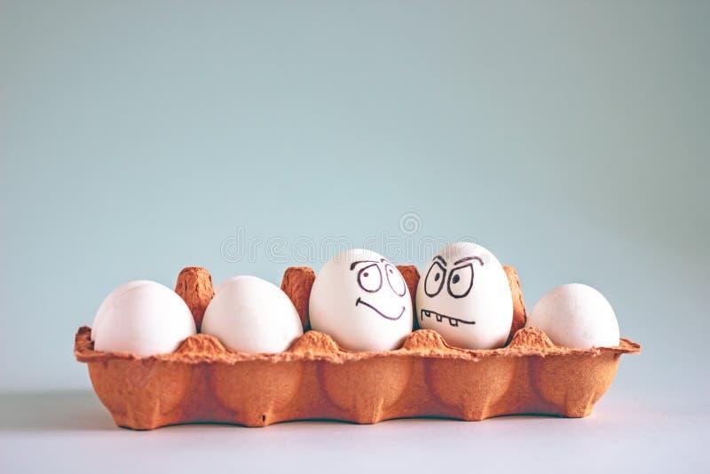 Uova bianche del pollo divertente con i fronti in una cellula dell'uovo immagine stock libera da diritti