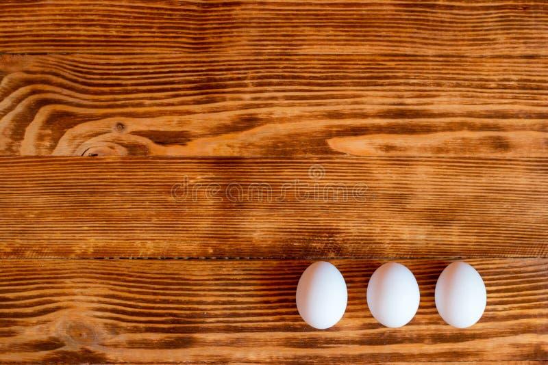 Uova bianche su un fondo di legno immagini stock libere da diritti