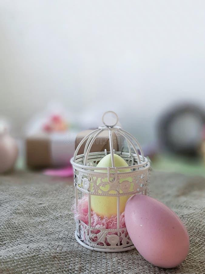 Uova colorate, gabbia decorativa sulla superficie della tela da imballaggio davanti a fondo bianco immagine stock libera da diritti