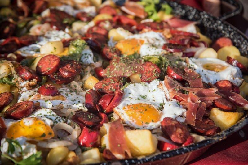 Uova cotte con chorizo, jamon e bacon nella pentola fine su focus4 selettivo immagini stock