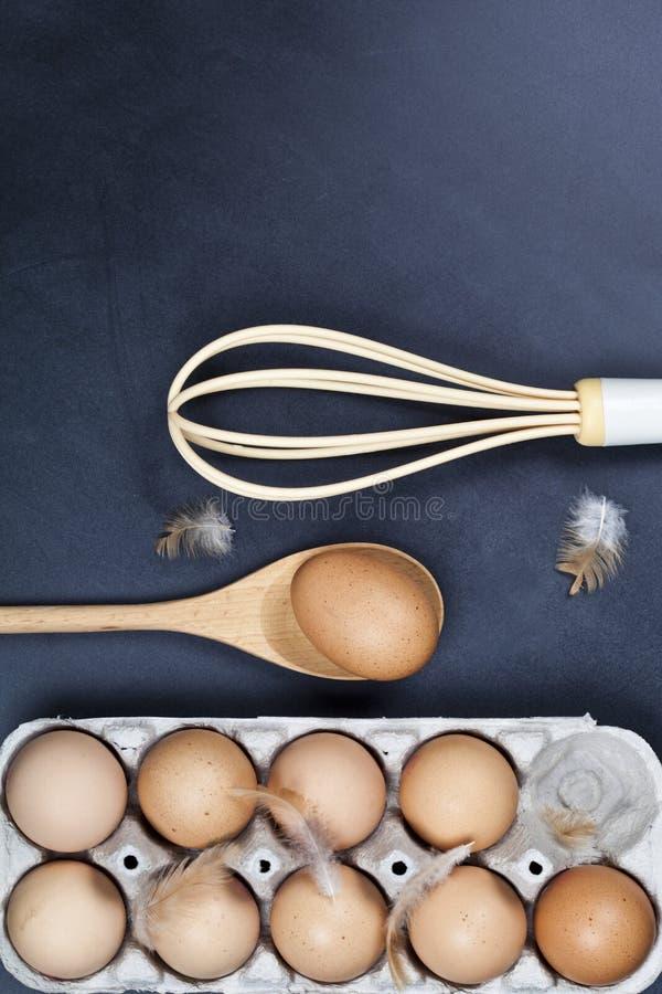 Uova, cucchiaio di legno, basette e piume immagini stock