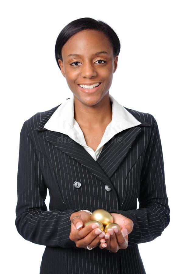 Uova dell'oro della holding della donna fotografia stock
