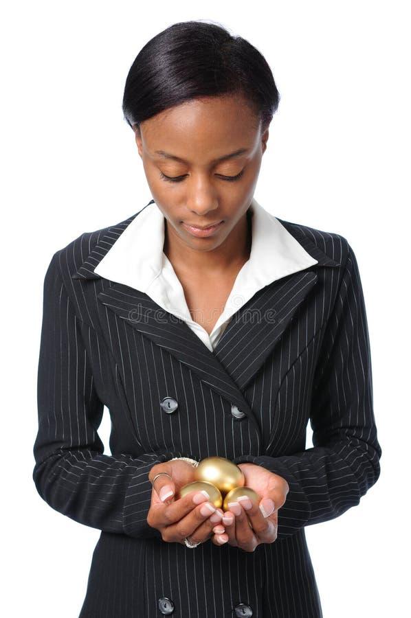 Uova dell'oro della holding della giovane donna fotografie stock libere da diritti