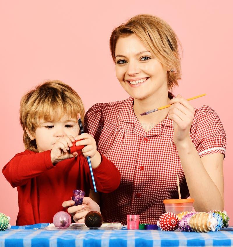 Uova della pittura del figlio e della madre per Pasqua fotografia stock libera da diritti