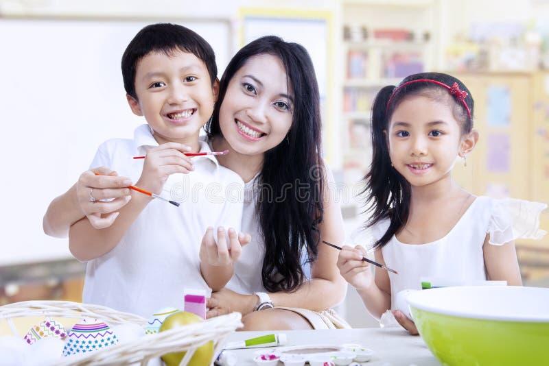 Uova della pittura della famiglia nella classe immagine stock libera da diritti