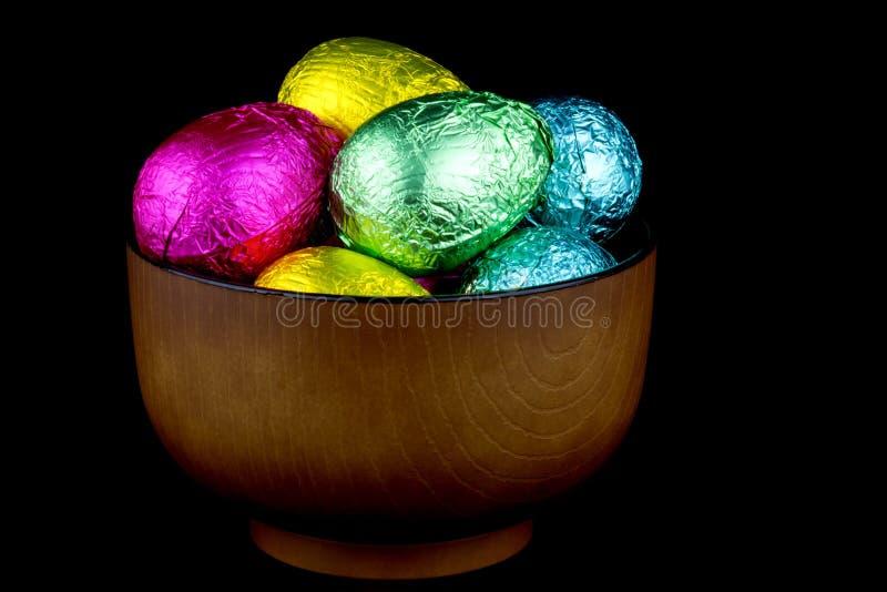 Uova di cioccolato in imballaggio leggero in una ciotola di legno sul nero fotografia stock