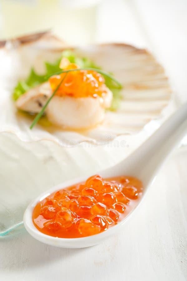 Uova di color salmone sopra il cucchiaio fotografia stock