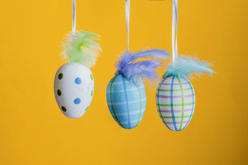 Uova di colore di Pasqua su un fondo giallo fotografia stock libera da diritti