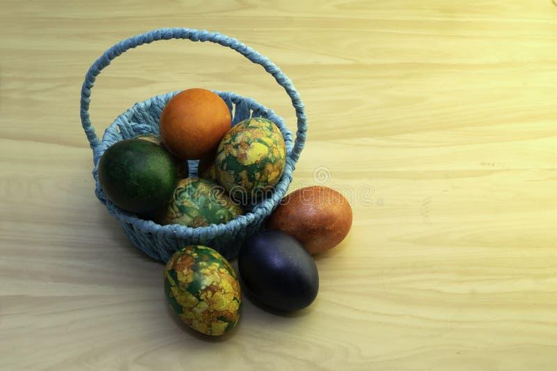 Uova di Pasqua che si trovano su una tavola di legno gialla ed in un canestro blu, paste della copia fotografia stock libera da diritti