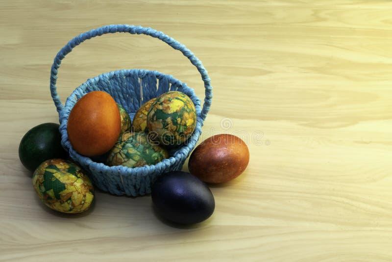 Uova di Pasqua che si trovano su una tavola di legno gialla ed in un canestro blu, paste della copia immagini stock libere da diritti