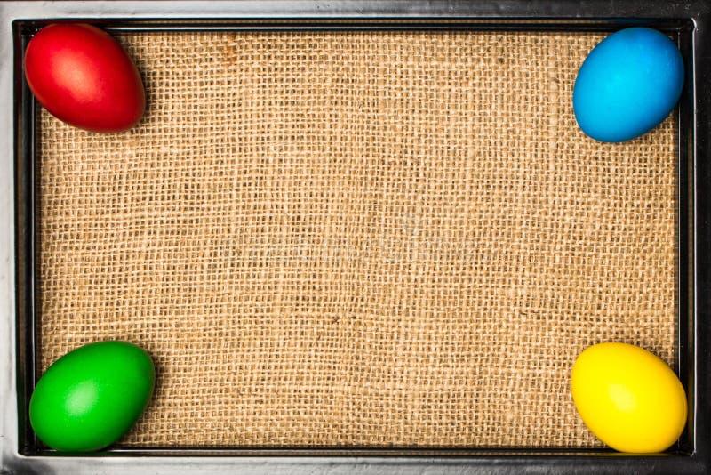 Uova di Pasqua colorate nel telaio nero del metallo, fondo rustico immagine stock libera da diritti