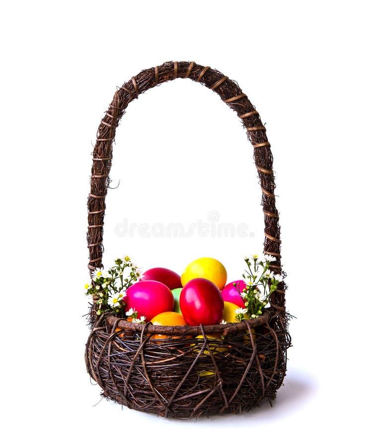 Uova di Pasqua Colourful in canestro marrone fotografie stock libere da diritti
