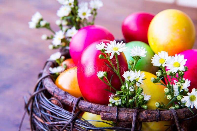 Uova di Pasqua Colourful in canestro marrone fotografie stock
