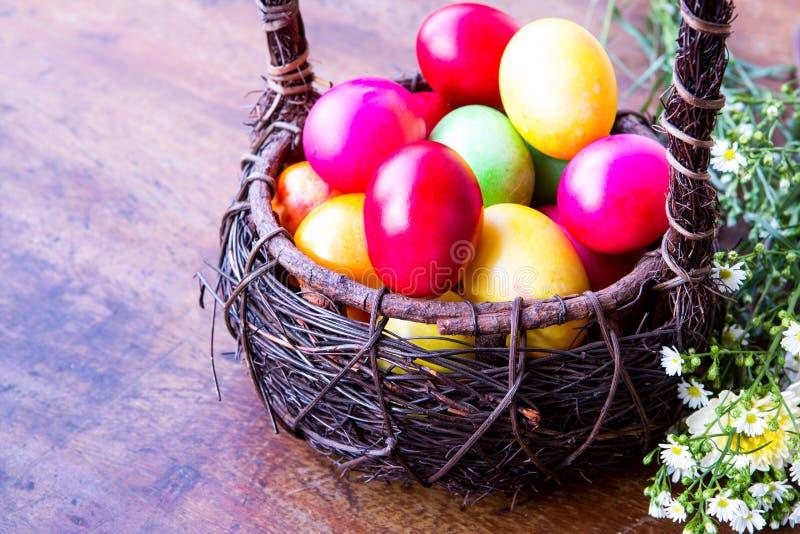 Uova di Pasqua Colourful in canestro marrone immagini stock libere da diritti