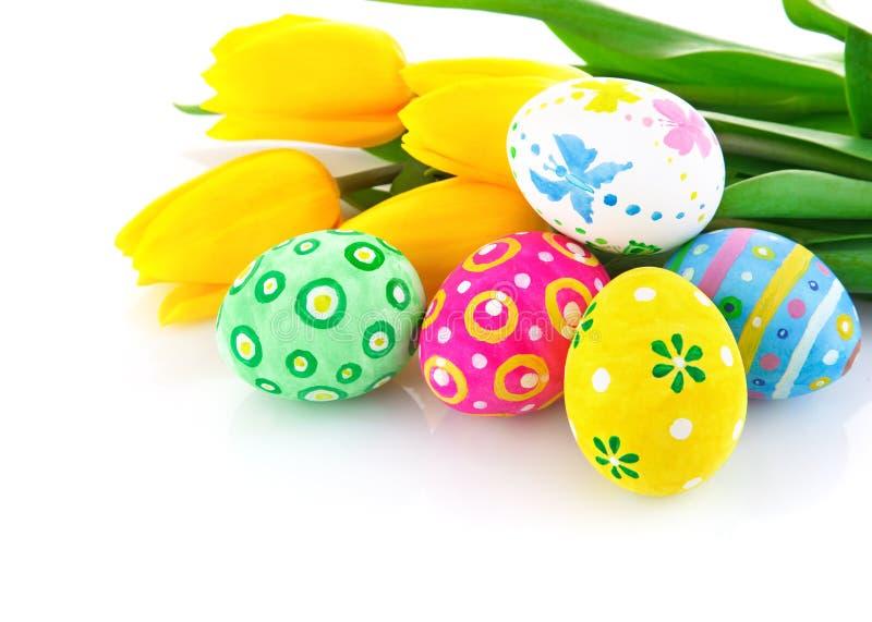 Uova di Pasqua Con i fiori gialli del tulipano immagini stock