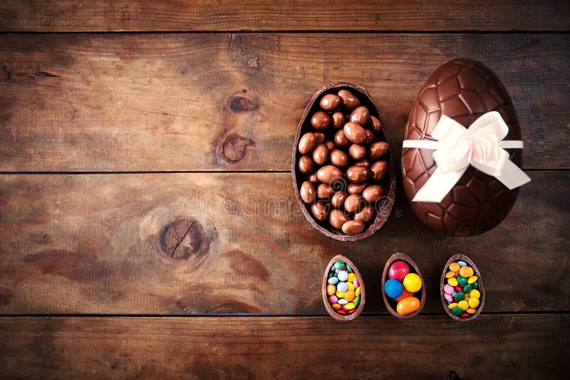 Uova di Pasqua del cioccolato su fondo di legno scuro con il ribbo di colore immagine stock