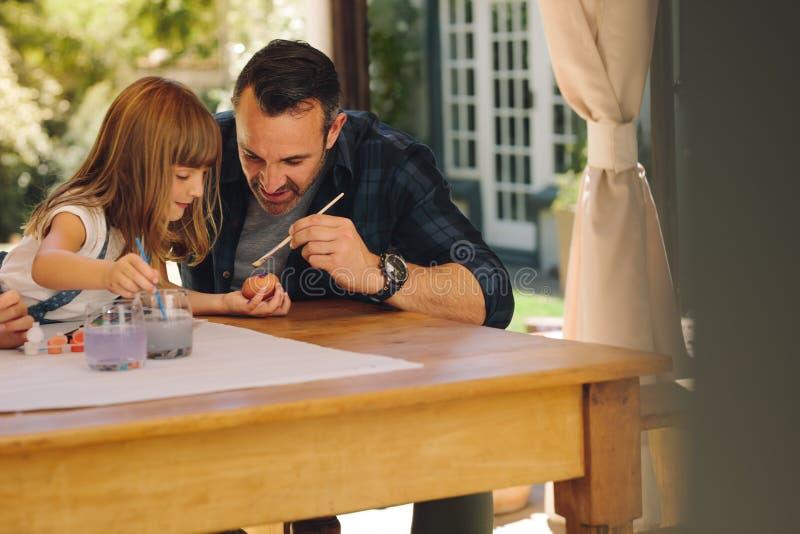 Uova di Pasqua della pittura della figlia e del padre insieme immagini stock libere da diritti