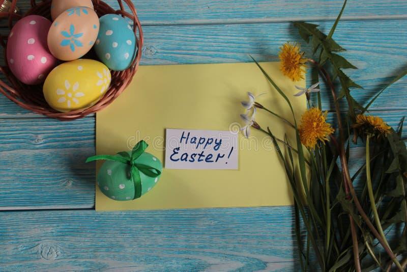 Uova di Pasqua dipinte in canestro intrecciato, su un fondo blu immagine stock libera da diritti