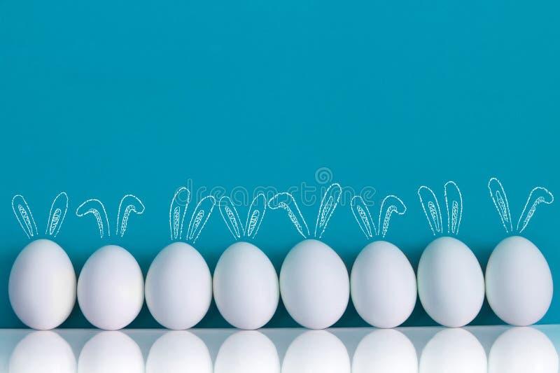 Uova di Pasqua dipinte con le orecchie di conigli e i ballooons sui precedenti blu fotografia stock