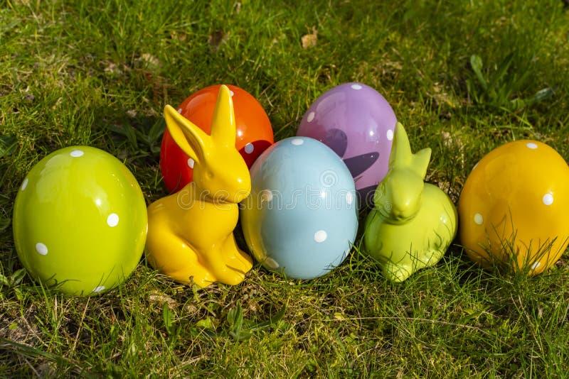 Uova di Pasqua e coniglietti di pasqua ceramici su un prato fotografie stock