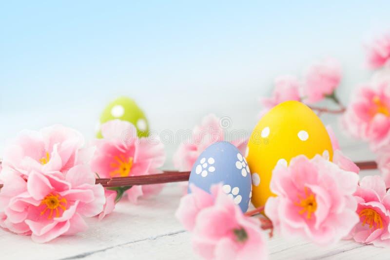 Uova di Pasqua e decorazione rosa dei fiori su fondo blu immagini stock libere da diritti