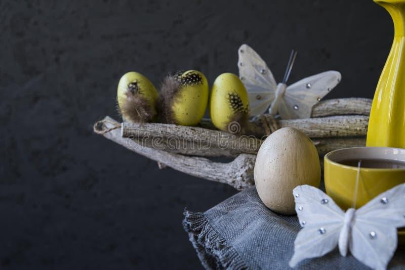 Uova di Pasqua gialle, farfalle bianche sul ramoscello Fondo nero, spazio per testo immagine stock libera da diritti