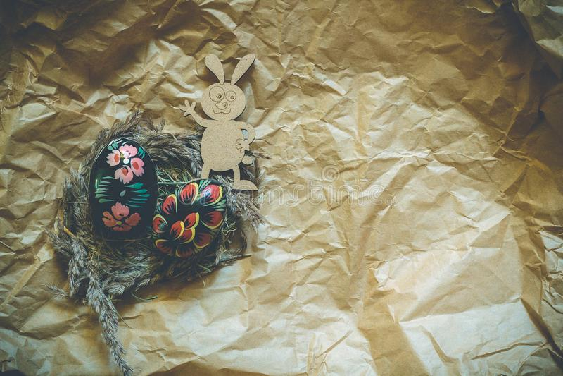 Uova di Pasqua di legno variopinte e coniglio di legno del fanny su un fondo della carta del mestiere modificato immagini stock