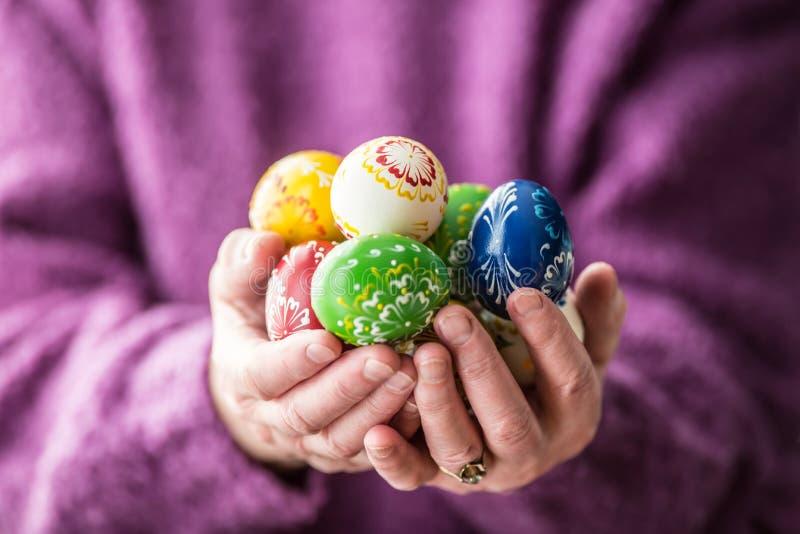 Uova di Pasqua multicolori del primo piano nelle mani senior della donna fotografie stock