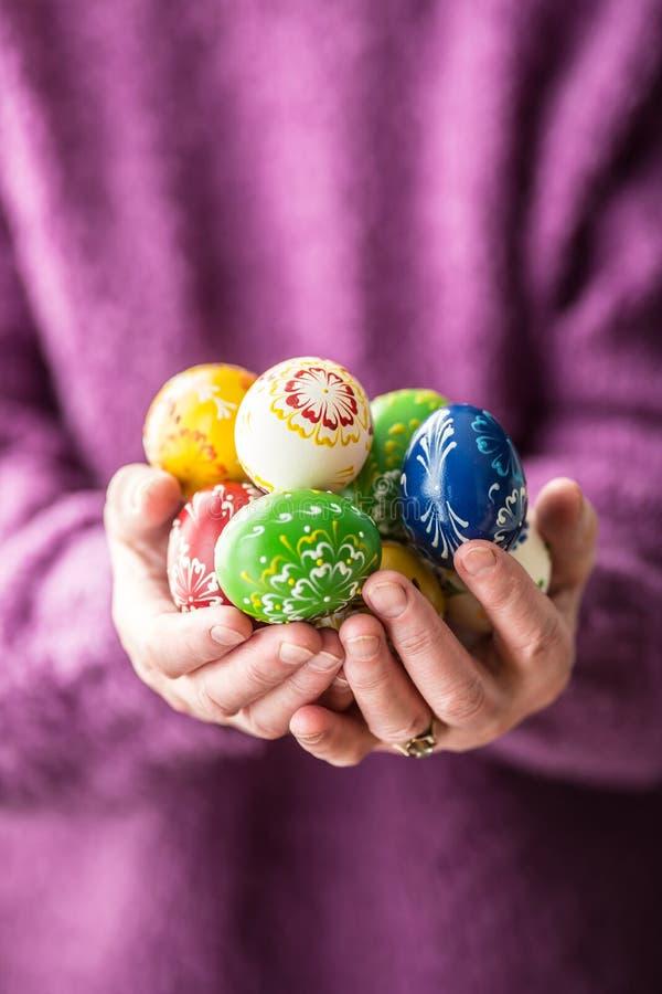 Uova di Pasqua multicolori del primo piano nelle mani senior della donna fotografia stock libera da diritti