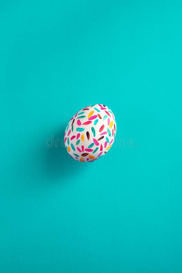 Uova di Pasqua multicolori divertenti dipinte a mano con le spazzole, su fondo blu fotografie stock