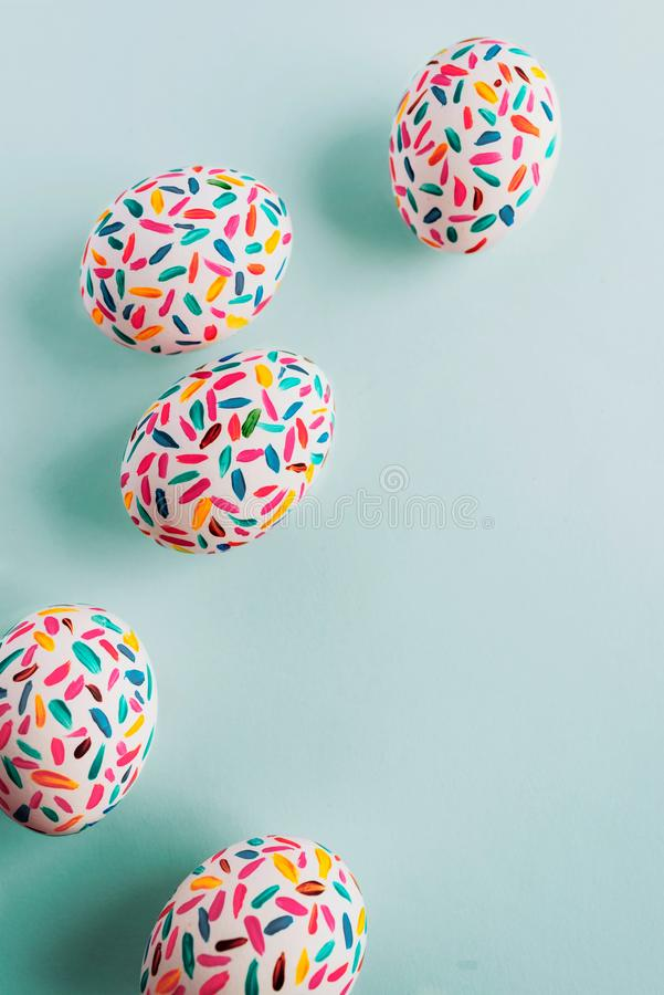 Uova di Pasqua multicolori divertenti dipinte a mano con le spazzole, su fondo blu molle fotografia stock