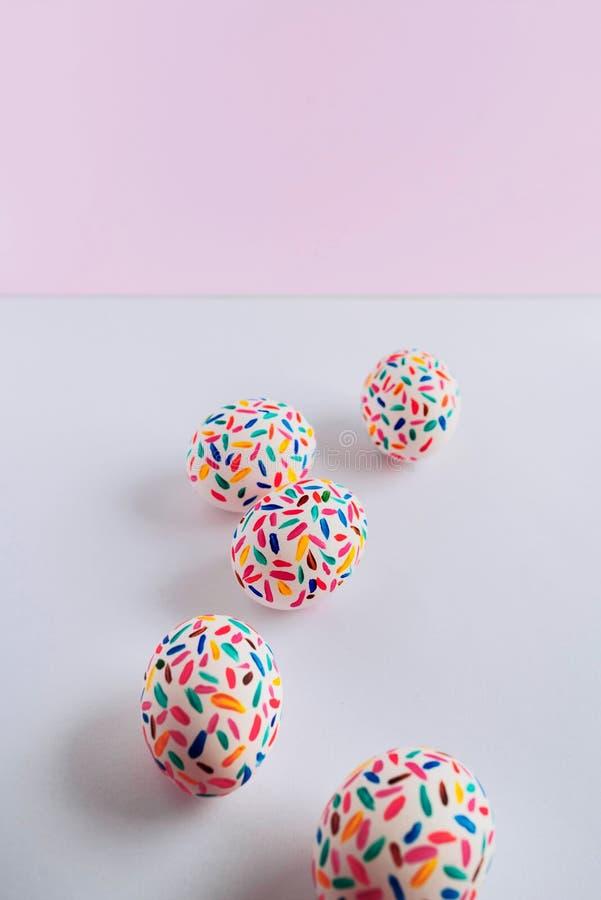 Uova di Pasqua multicolori divertenti dipinte a mano con le spazzole, su fondo rosa molle fotografia stock libera da diritti