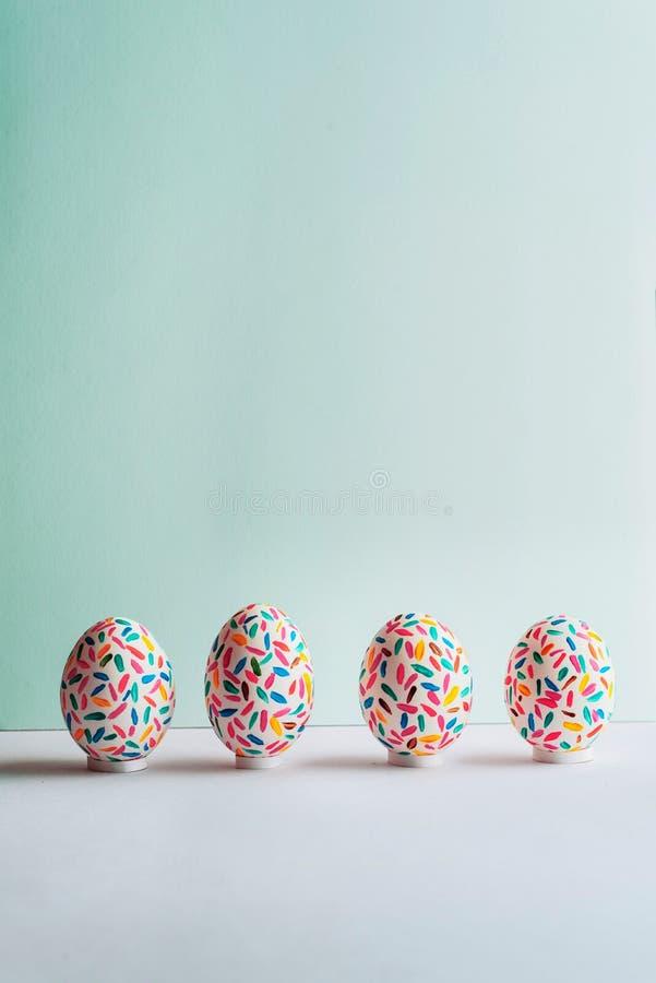 Uova di Pasqua multicolori divertenti dipinte a mano su fondo blu molle, vista frontale immagine stock
