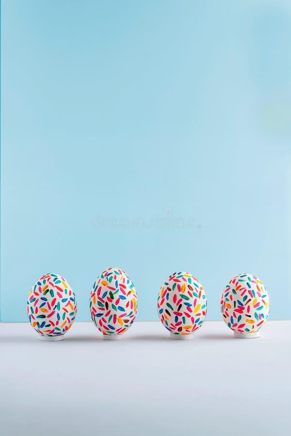 Uova di Pasqua multicolori divertenti dipinte a mano su fondo blu molle, vista frontale immagini stock libere da diritti