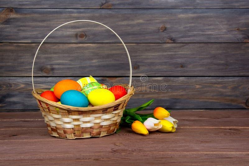 Uova di Pasqua nei tulipani rossi e gialli di vimini del canestro, sui bordi di legno immagine stock
