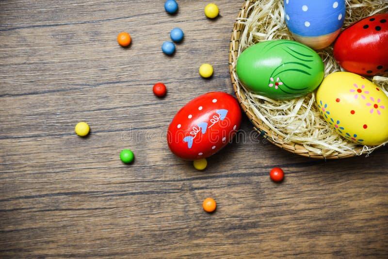 Uova di Pasqua nel canestro del nido sul fondo di legno della tavola rustica/uova variopinte dipinte decorati immagine stock