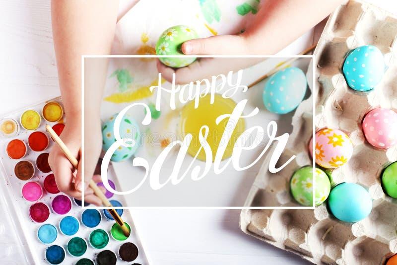 Uova di Pasqua, pitture e spazzole bollite dipinte a mano del bambino su una tavola bianca Preparazione per la festa Le mani dell immagine stock libera da diritti