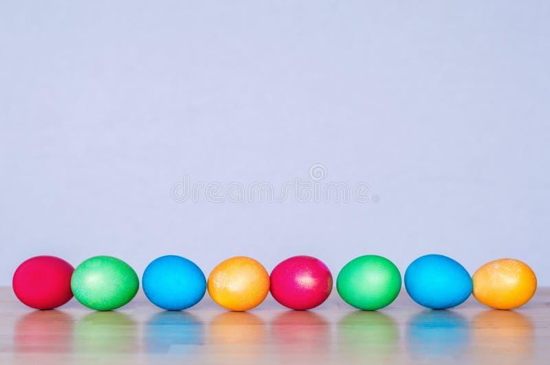 Uova di Pasqua risiedute in una fila fotografie stock