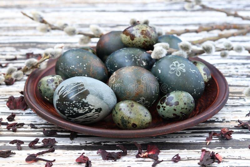 Uova di Pasqua su un piatto, dipinto con tè dai petali di una rosa o di un ibisco sudanese fotografie stock