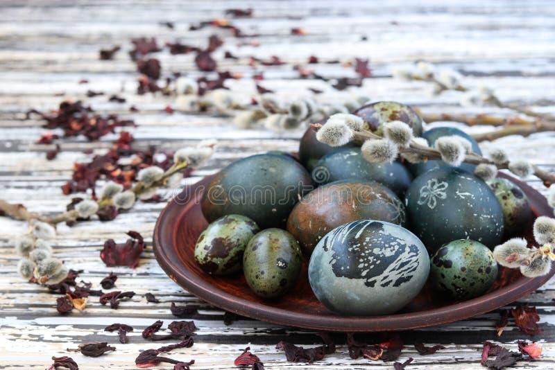 Uova di Pasqua su un piatto, dipinto con tè dai petali di una rosa o di un ibisco sudanese immagini stock