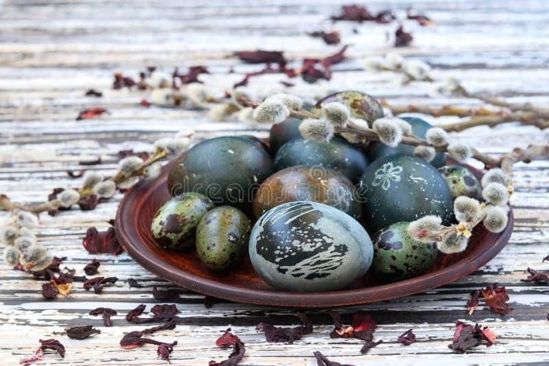 Uova di Pasqua su un piatto, dipinto con tè dai petali di una rosa o di un ibisco sudanese fotografia stock